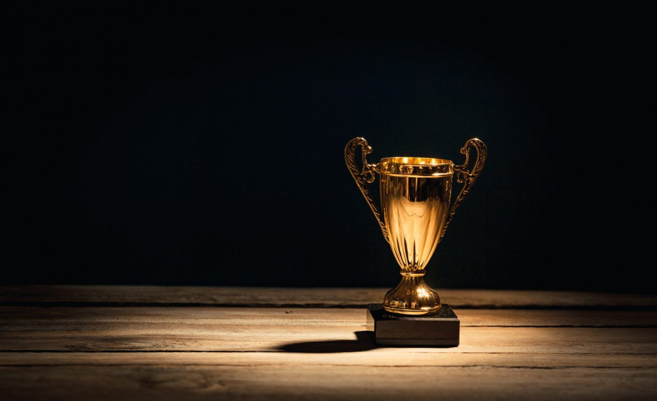 https://pccbd.com/wp-content/uploads/2020/05/golden-sports-trophy-cup-on-wood-desk-with-dramatic-strong-contrast-light-and-shadow_t20_doQNmj-1280x781.jpg