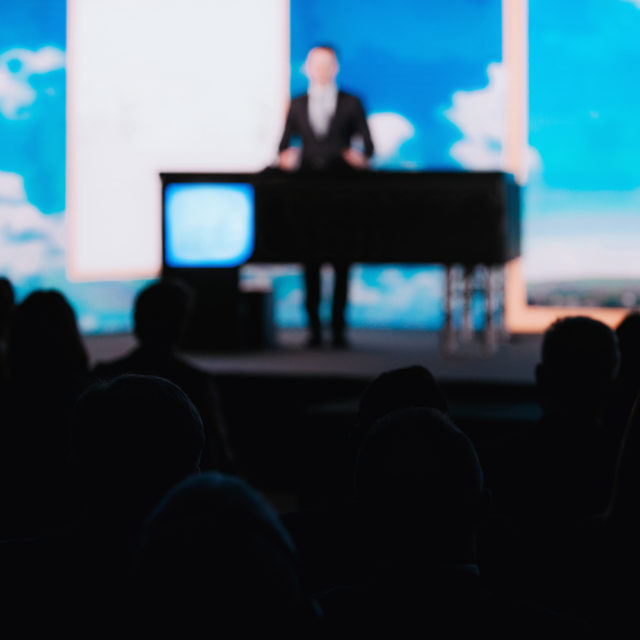 Blurred male speaker on the stage wearing suit, audience silhouettes listening presentation, blue background